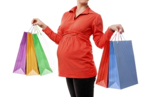 Pregnant woman holding shopping bags isolated